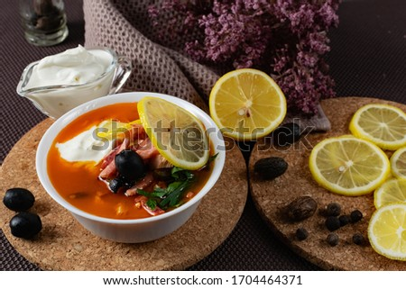 Soup Solyanka is a combined meat soup with smoked meat , various types of meat and tomato paste, serving dishes with sour cream, lemon and fresh herbs Stock fotó ©