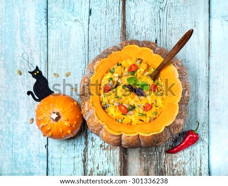 Soup with lentil in the carved pumpkin and black cat toy on the blue wooden background at Halloween party