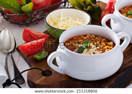 Soup with lentils, pasta and tomatoes topped with cheese