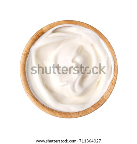 Sour cream in a wooden bowl isolated on white. Dairy product. Top view.