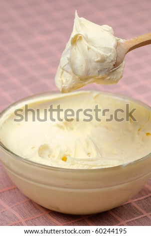 Sour cream in bowl with wooden spoon after cooling