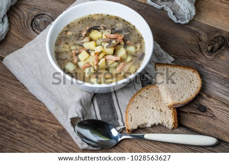 Sour rye soup with potatoes, mushrooms and smoked meat.