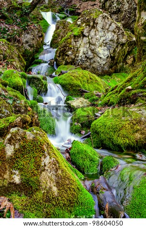 Source water flowing over rocks - stock photo