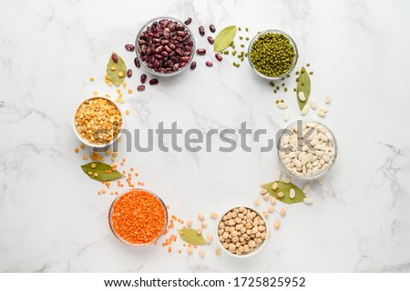 Sources of vegetable protein. Different types of beans and cereals in bowls form a circle. Vegan and vegetarian food concept. Copy space, flat lay. Light marble background. Stockfoto ©