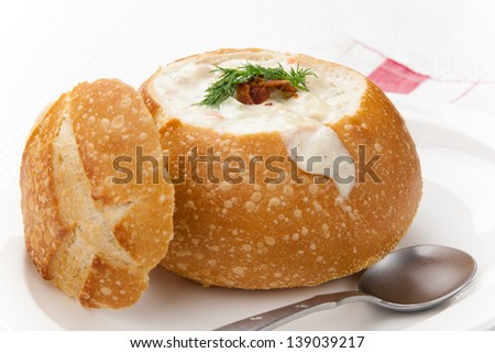 Sourdough bun of delicious hot clam chowder garnished with bacon, and dill.