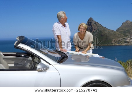 South Africa, Cape Town, senior couple standing by car with map, smiling, sea in background