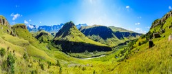 South Africa Drakensberg scenic panoramic impressive landscape view -  green Giants Castle wide panorama with sunny blue sky - mountains valley,creek,grass, bright,horizon,clouds,travel,stunning