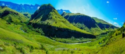South Africa Drakensberg scenic panoramic impressive landscape view -  green Giants Castle wide panorama,sunny blue sky,mountain,hill, valley, creek, grass, bright weather, horizon, cloud,travel,bench