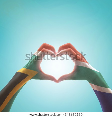 South Africa flag color pattern on woman human hands in heart shape on vintage sky background: Hand sign language symbolic concept of national unity, union, love for the nation and reconciliation