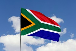South Africa flag isolated on the blue sky with clipping path. close up waving flag of South Africa. flag symbols of South Africa.