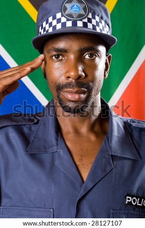 south africa policeman saluting, background is south african flag - stock photo