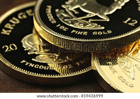 South African 1 ounce gold bullion coins on wooden Background