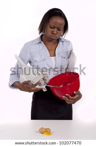 South African woman struggling with a mess she made in the kitchen.