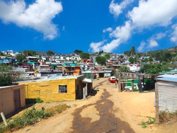South Africans walking on the street of colorful informal settlements,huts made of metal in the Township or Cape Flats of Stellenbosch,Cape Town, South Africa with blue sky and clouds background, Slum