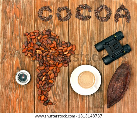 "South America continent made of cocoa beans, the word ""cocoa"" made of cacao nibs, binoculars, compass, cocoa pod with cup of cacao drink on wooden background. Top view."