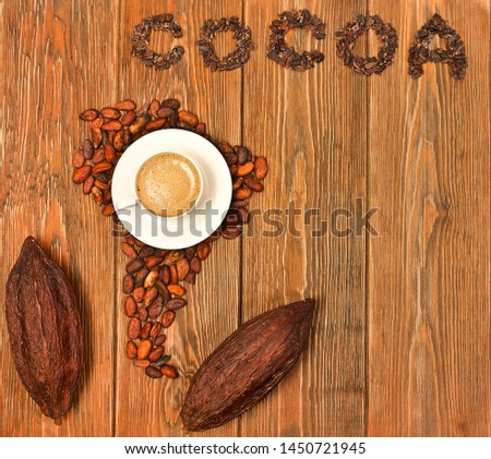 "South America continent made of cocoa beans, the word ""cocoa"" made of cacao nibs, cup of cacao drink with cocoa pods on a wooden background. Top view."