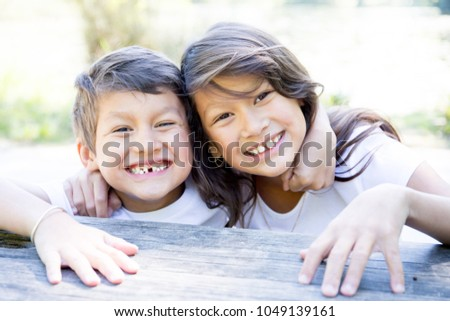south american happy Brother and sister sitting outside together in the park #1049139161