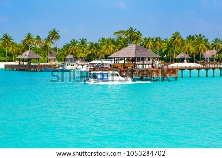South Ari Atoll, Dhidhoofinolhu, Maldives - 8 July 2017: Powerboats for guests and tours near overwater wooden pier on the sabdy beach in  Maldives island, 8 July 2017 #1053284702