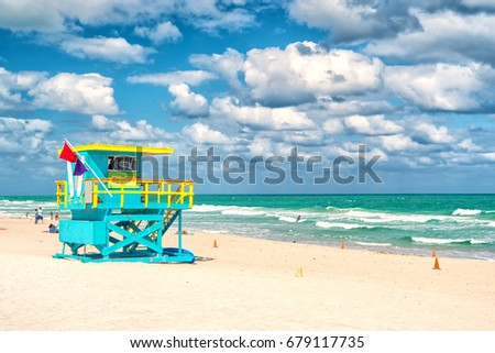 South Beach, Miami, Florida, lifeguard house in a colorful Art Deco style blue and yellow on cloudy blue sky and Atlantic Ocean in background, world famous travel location