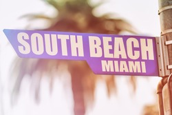 South Beach Miami Street Sign. A street sign marking South Beach, Miami. Backed by a palm tree with a sunset flare.