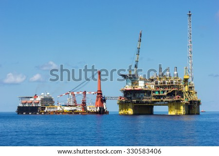 South China Sea, Malaysia - June 4: Supply vessel and oil rig platform on calm blue sea. South China Sea, Malaysia, June 4th, 2015