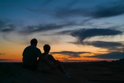 South Dakota Badlands. Romantic couple silhouetted against a beautiful sunset on mountain top