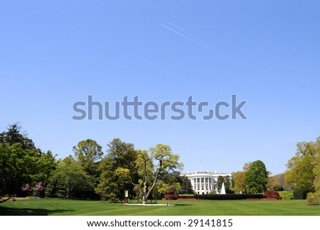 South facade and South lawn of the White House in Washington DC in spring colors, with paths of two airplanes crossing high up in the sky, and ample copyspace in the sky