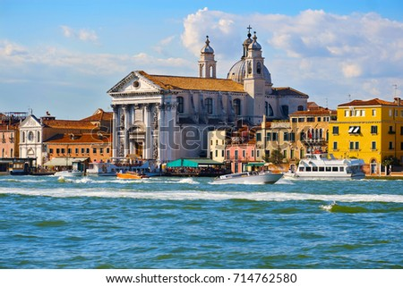South facade of the cathedral of Santa Maria della Salute in Venice, Italy. Beautiful view of the Grand Canal buildings with gondolas and colorful facades of old medieval houses in Venice. #714762580