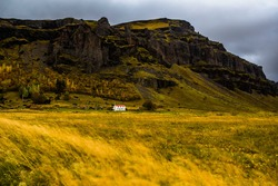 South Iceland landscape with Nupsstadur historic turf house farm in the distance at the base of the volcanic rock hills with autumn colors decorating the trees in the small forest behind the farm