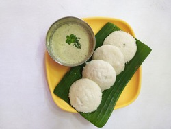 South Indian breakfast well known as idly and green coconut chutney serve on banana leaves on a white background for gradient text space
