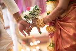 South Indian Ceylonese couple linking pinky fingers on wedding day
