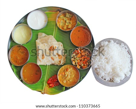 South indian plate meals on banana leaf isolated on white. Traditional vegetarian wholesome indian food with variety of curries, rasam, sambar, rice, subzi and chapatti(chapathi) or roti(phulka).