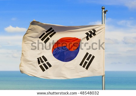 south korean flag on a pole against beautiful sky over horizon on water