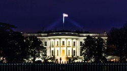 South lawn view of the White House, presidential residence at night in winter with the structure illuminated and steel fence in the foreground.