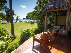 South Pacific Tropical Island Bure Bungalow Deck with Day Bed Looking over Garden, Oceans and Over Water Bure in Fiji
