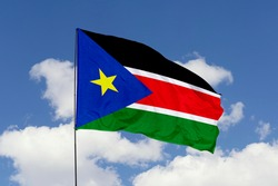 South Sudan flag isolated on the blue sky with clipping path. close up waving flag of South Sudan. flag symbols of South Sudan.