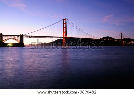 South tower of Golden Gate Bridge glows against beautiful sunset sky with Fort Point lit by fluorescent floodlight.
