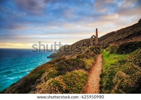 South West Coast Path as it approaches the ruins of the Wheal Coates mining engine house near St Agnes in Cornwall. #625950980