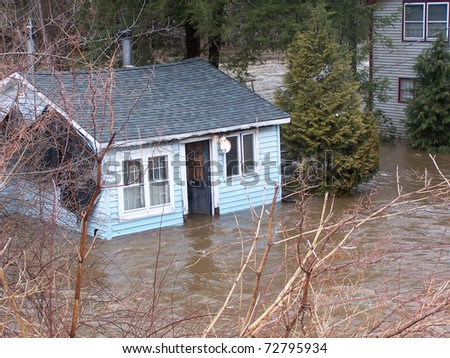 SOUTHBURY, CONNECTICUT - MARCH 7: Flooding cottage along the Pomperaug River on March 7, 2011 in Southbury, CT. The neighborhood is being evacuated due to the vast rainfall and the rising river. - stock photo