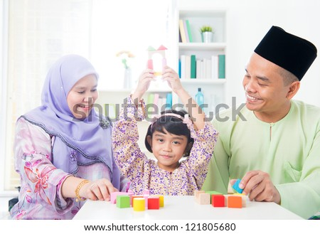 Southeast Asian child achievement. Muslim family playing games.
