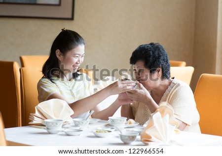 Southeast Asian Chinese family having meal in restaurant