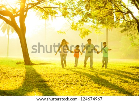 Southeast Asian Chinese family holding hands, running at outdoor green park during sunrise