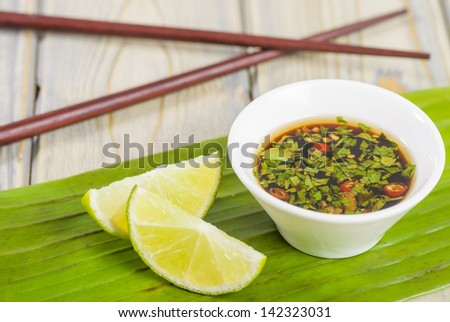 Southeast Asian dipping sauce with chilli coriander and fish sauce and lime wedges.