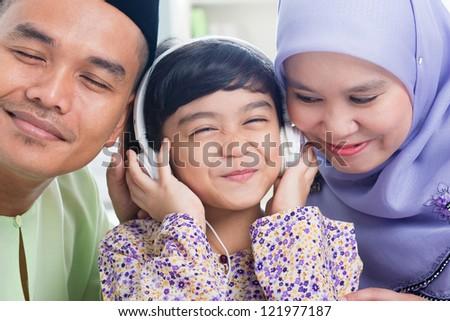 Southeast Asian family listen mp3, sharing headphone. Muslim family living lifestyle