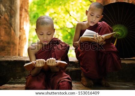 Southeast Asian Myanmar little monk reading book outside monastery, Buddhist teaching.