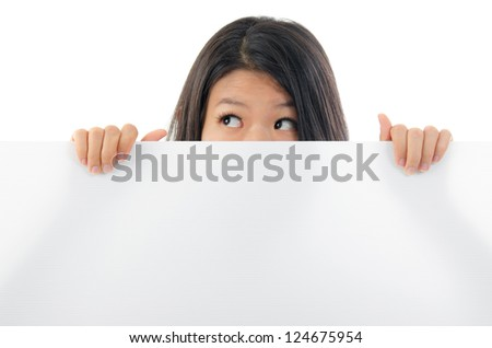 Southeast Asian woman eyes opened big looking side holding a placard, hiding behind and covering mouth.