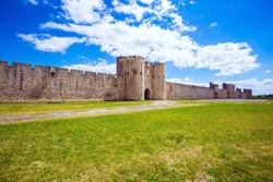 Southern France. Picturesque powerful gates and fortifications defend the port city of Aigues-Mortes. Journey to History. Around the walls are green lawns