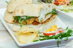 Southern fried chicken breast with ham, cheese, lettuce and garlic mayo in ciabatta bread with salad and crisps
