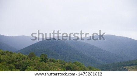 Southern highlands. Field with low mountains. Low mountains with trees. Anapsky district, Russia. Summer mountain landscape
