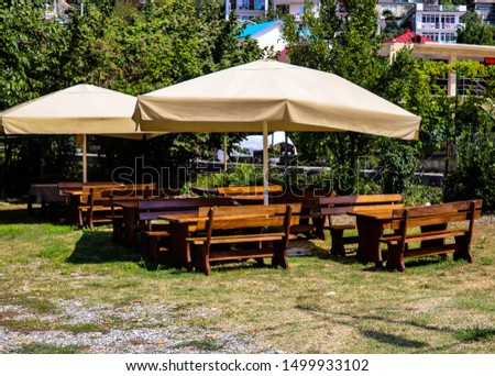 southern outdoor cafe. wooden furniture. modern interior. food outdoors. breakfast, lunch, dinner.